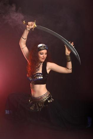 Belly dancer Jade lunging with scimitar