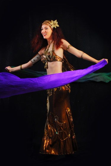 Beautiful belly dancer spinning with silk veils