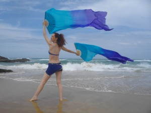 Belly dancing with fan veils at the beach